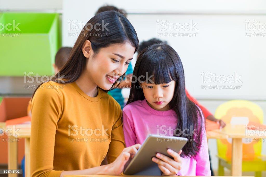 亞洲女教師在幼稚園學前教育、網路教育理念的課堂上教女學生用平板電腦。圖像檔