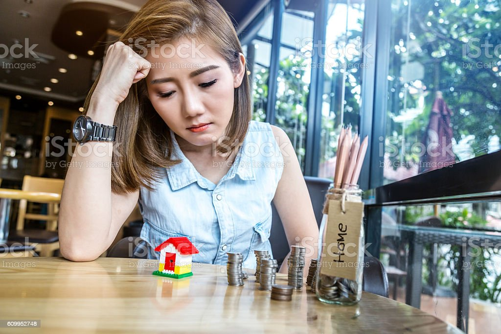 asia woman with house model and money bottle stock photo