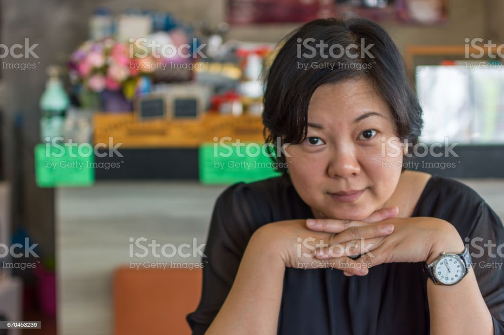 Asia women 40s white skin in black dress have a lovely thao chin gesture in a coffee shop cafe stock photo