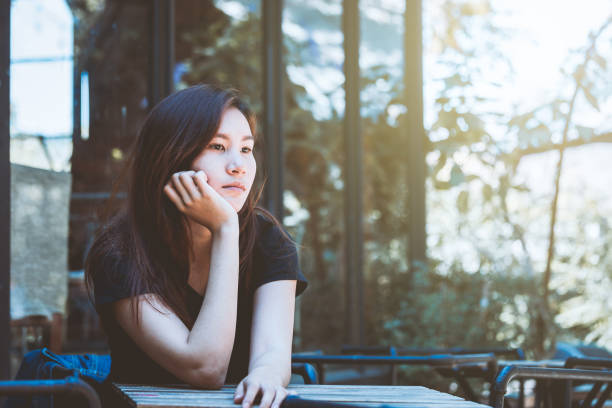 asia youth teenager sitting depression on chair. lifestyle people concept in cafe. - east asian ethnicity stock photos and pictures