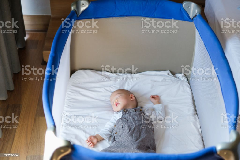 Asian 1 year old toddler baby boy child sleeping in baby cot near parent's bed in bedroom stock photo