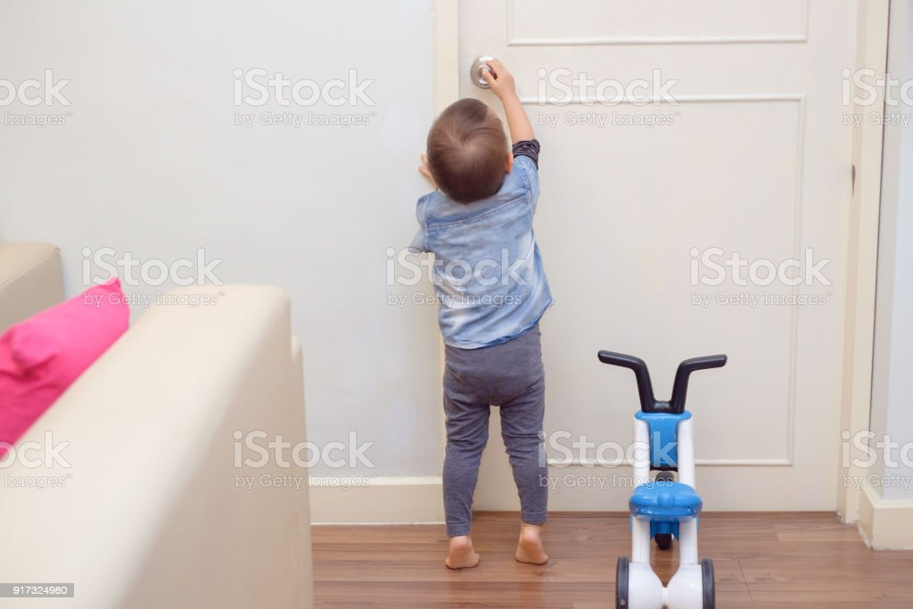 Asian 18 months / 1 year old toddler baby boy standing on tiptoes at home, Kid reaching up try to open / close door knob stock photo