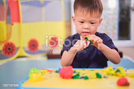 istock Asian 2 - 3 years old toddler boy child having fun playing colorful modeling clay / Play dough at home, Educational toys for kid 1207137328