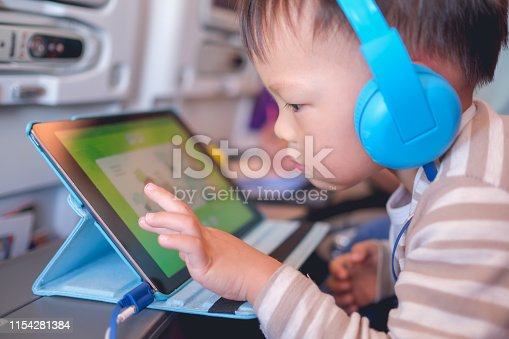 Cute Asian 2 - 3 years old toddler boy child wearing headphones using tablet pc watching cartoons / playing game during flight on airplane. Happy Flying with children concept, soft & selective focus