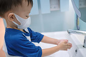 Cute little Asian 3 - 4 years old toddler boy child wearing protective medical mask washing hands by himself on sink in public toilet / bathroom for kids, Sanitation concept - soft & selective focus