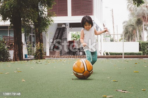 istock Asian 3 year old kid play football in park. 1288179148