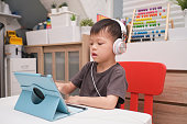 Asian 4 years old toddler boy child using tablet pc computer, Child at home, kindergarten closed during the Covid-19 health crisis, Distance Learning, Online Games, Activities for Kindergarten concept