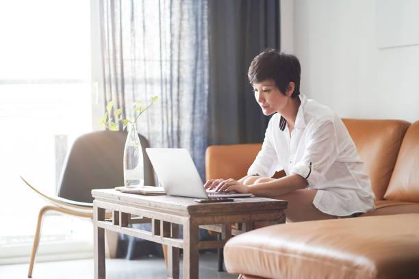 asiatische erwachsenen-schönheit auf couch und arbeit auf laptop von zu hause - telearbeit stock-fotos und bilder