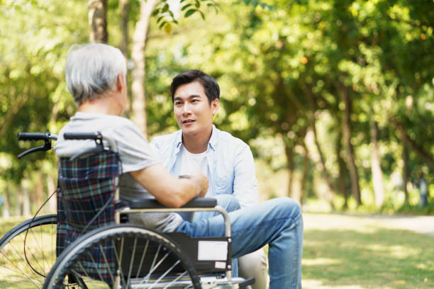 asian adult child talking to senior father outdoors stock photo