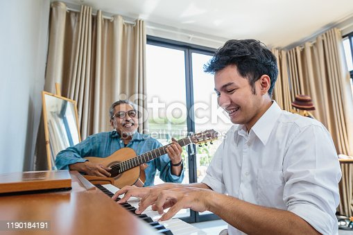 Asian adult son enjoy playing piano and senior father playing guitar together in living room at home
