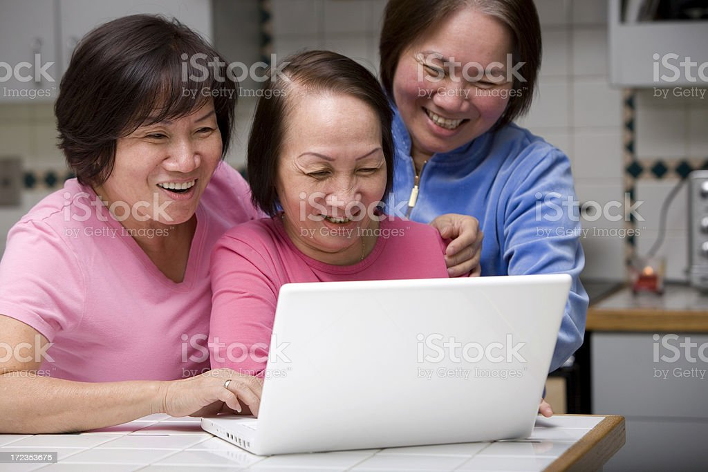 Asian Adult Women Laughing and Smiling, Using Laptop in Kitchen royalty-free stock photo