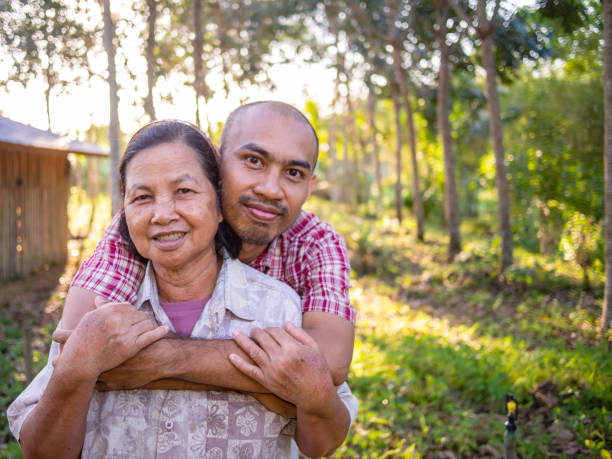Asiatischer Landwirt, Mutter und Sohn, sitzenauf dem Hof. – Foto