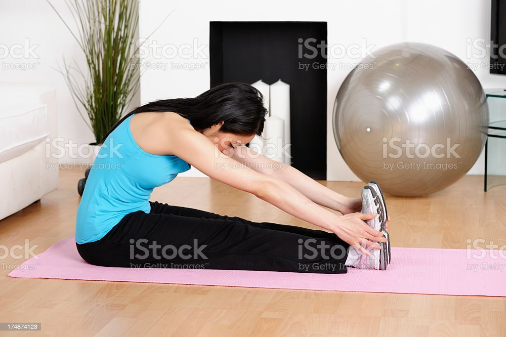 Asian American/ Oriental Woman Doing Stretch Exercises At Home royalty-free stock photo