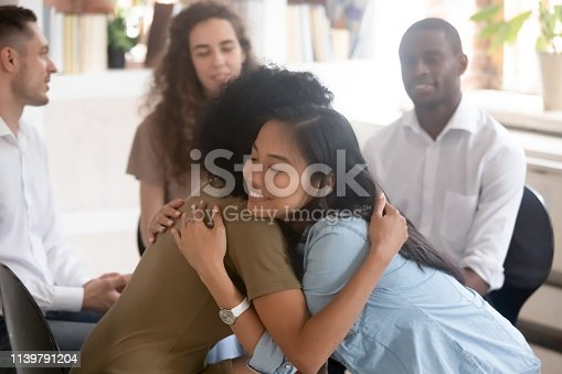 511741068 istock photo Asian and african women embracing giving psychological support during therapy 1139791204
