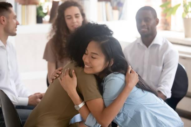 asiatische und afrikanische frauen, die sich für die psychologische unterstützung während der therapie einsetzen - danke an lehrerin stock-fotos und bilder