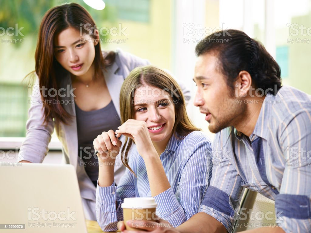 Asian And Caucasian Business People Working Together In Office Stock
