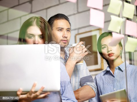 istock asian and caucasian business team working in office 855475140
