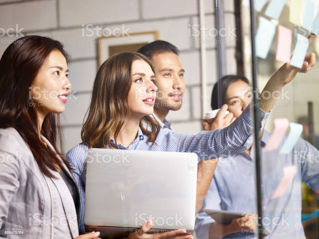 asian and caucasian business team working in office stock photo