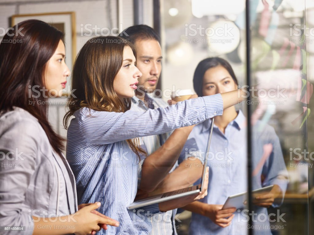asian and caucasian businesspeople meeting in office stock photo