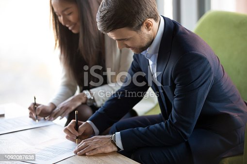 istock Asian and caucasian businesspeople sitting at desk signing contract 1092087638