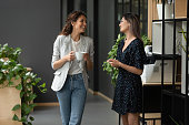 Asian and Caucasian ethnicity women colleagues met in office hall chatting enjoy friendly warm conversation, multi-ethnic mates having informal talk drink tea or coffee take break distracted from work