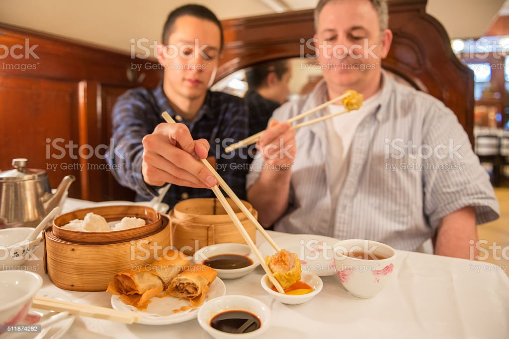 Asian and Caucasian Men Share Dim Sum Lunch in Restaurant stock photo