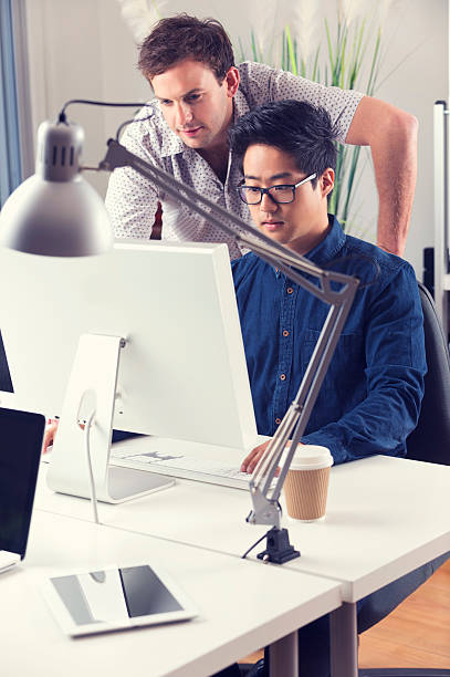 Asian and Caucasian men working together looking at computer stock photo