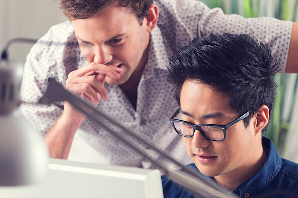 Asian and Caucasian men working together looking at computer. stock photo