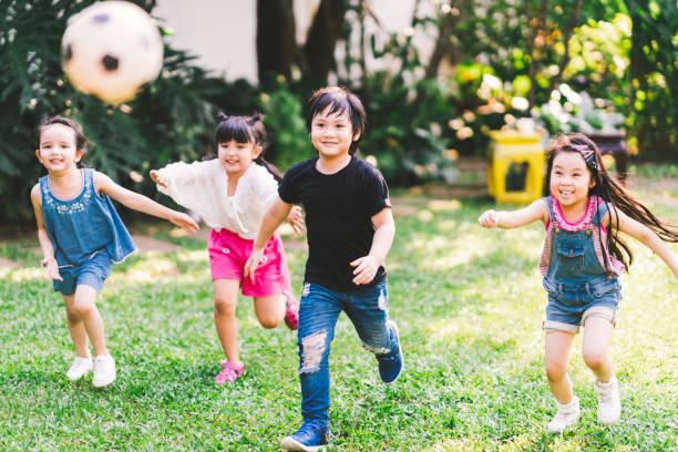 アジアと混合人種幸せな若い子供たちは、庭で一緒にサッカーをプレイしています。多民族の子供グループ、野外スポーツ運動、余暇ゲーム活動、または子供の頃の楽しいライフスタイルの� - 小学校 ストックフォトと画像