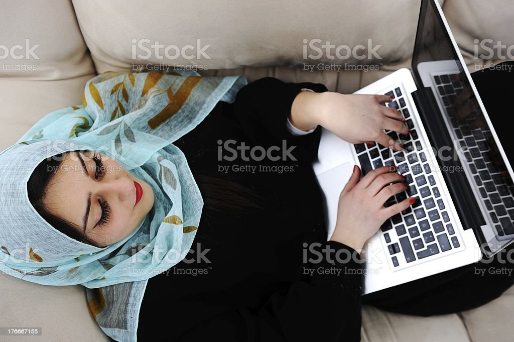 Asian Arabic young with laptop on sofa royalty-free stock photo