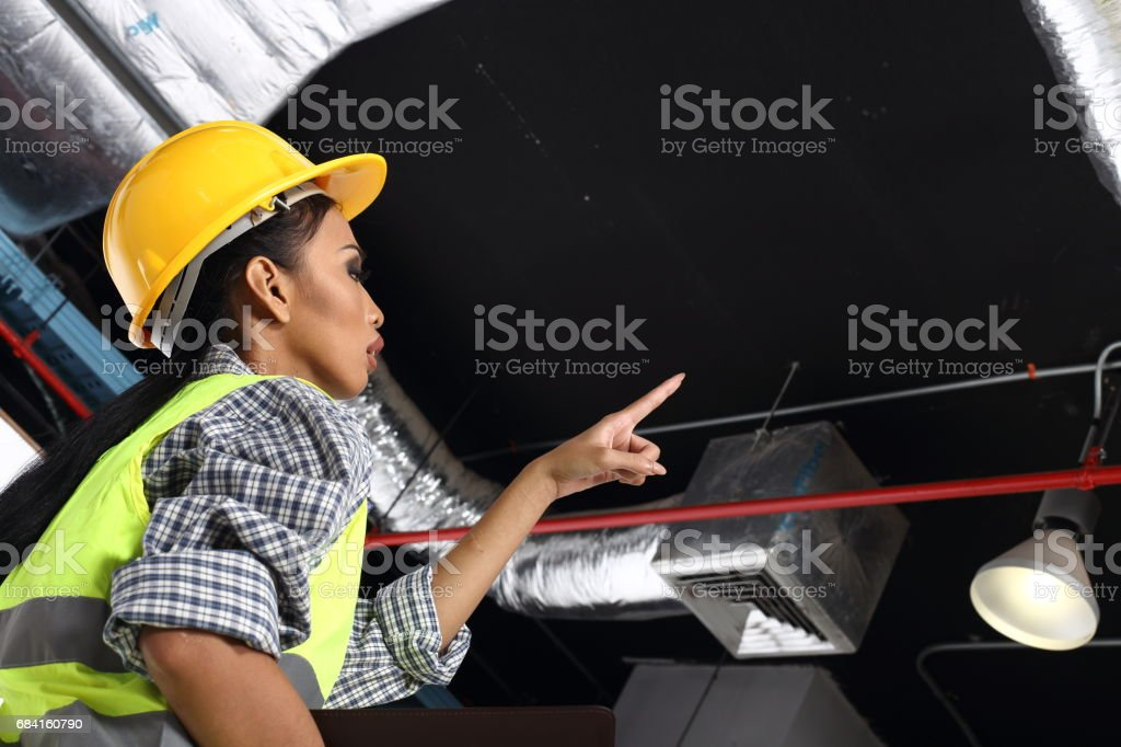 Asian Architect Engineer woman in yellow hard hat,  safety vast equipment, thick gloves, protector glasses goggle and equipment foto stock royalty-free