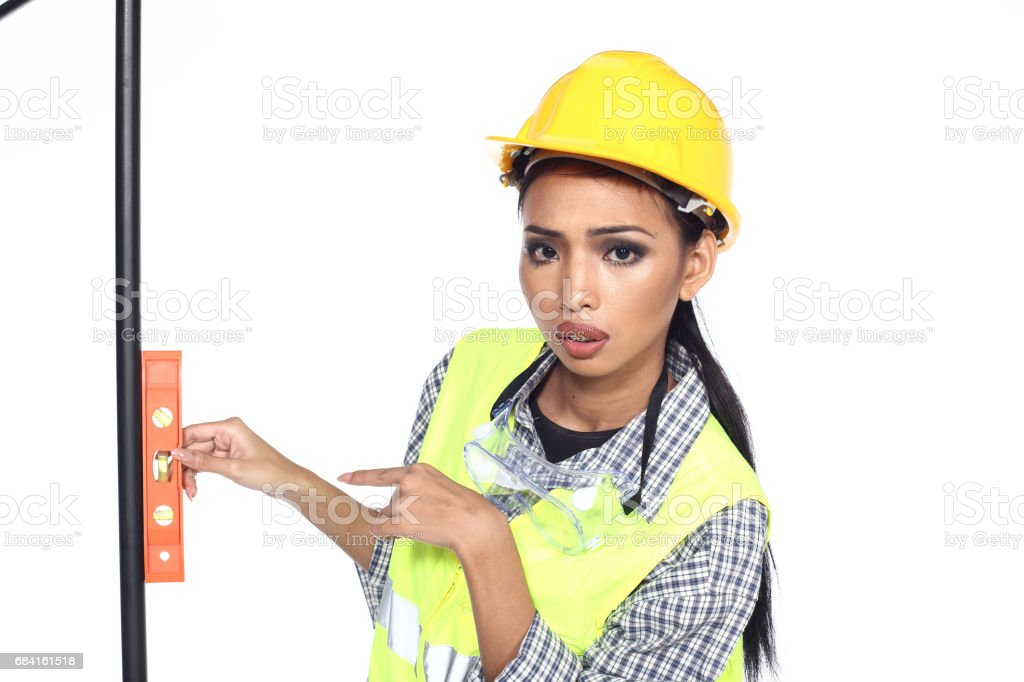 Asian Architect Engineer woman in yellow hard hat,  safety vast equipment, thick gloves, protector glasses goggle and equipment royalty-free stock photo
