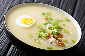 Asian Arroz Caldo rice soup with chicken, vegetables and egg close-up in a bowl on the table. horizontal