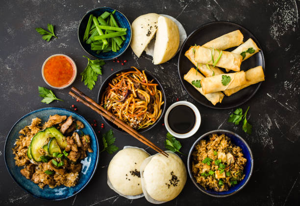 Asian assorted food set Asian assorted food set, dark rustic stone background. Chinese dishes. Chinese stir-fry noodles, asian rice with meat, dim sum, fried spring rolls, steamed Chinese buns. Top view. Asian stile dinner asian food stock pictures, royalty-free photos & images