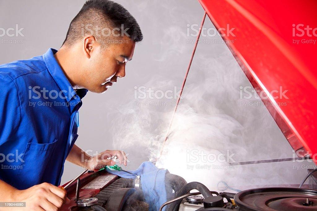 Asian automobile mechanic repairing motor vehicle. Open hood. Shop. royalty-free stock photo