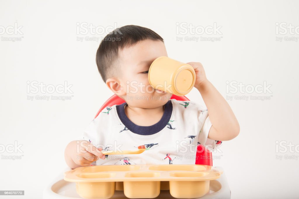 ASian baby boy sitting on the chair while eat and drink his meal time - Royalty-free Asia Stock Photo
