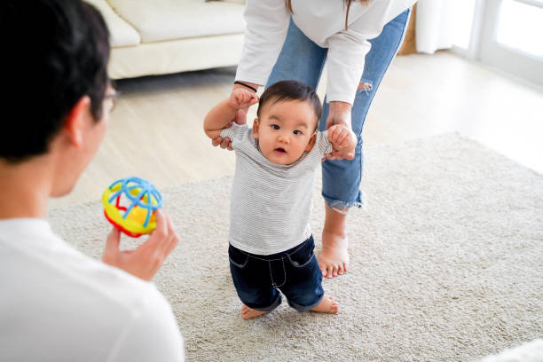 Asian baby boy toddler taking first steps. Family of father and mother encouraging their son learning to walk