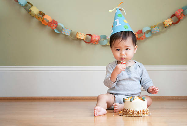 Asian baby celebrating his First Birthday Asian baby celebrating his First Birthday in front of his birthday cake at his birthday cake smash photoshoot. He's putting the birthday candle into his mouth.  first birthday stock pictures, royalty-free photos & images