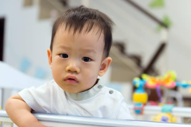 Asian baby cute boy in crib stock photo