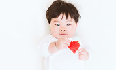 アジアのかわいい女の子は、バレンタインの背景の愛心を見せます。(ビンテージ トーン)