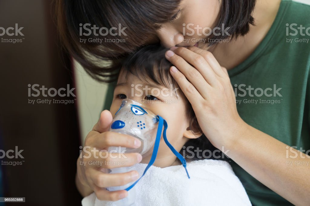 Asian baby girl breathing treatment with mother take care, at room hospital. royalty-free stock photo