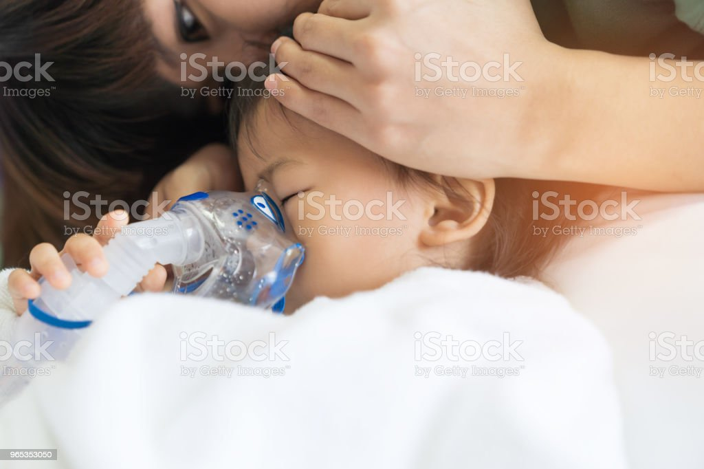 Asian baby girl breathing treatment with mother take care, at room hospital. zbiór zdjęć royalty-free