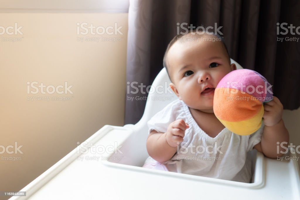 Asian Baby Girl Playing And Cuddling Colorful Ball On High Chair