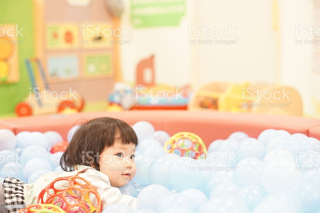 Asian baby girl playing in a ball pool stock photo