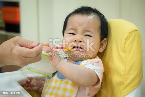 Asian baby girl refusing to eat food.tradition weaning