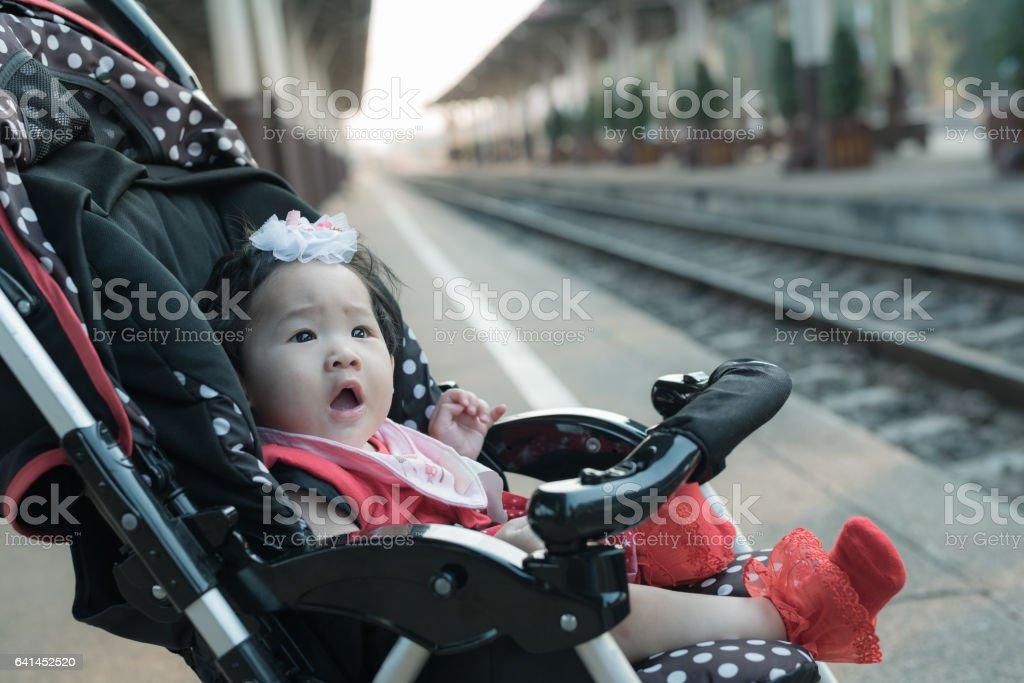 Asian baby girl sitting in stroller in railway station. stock photo