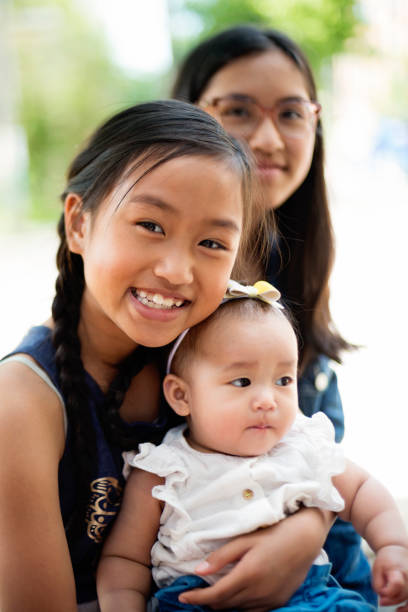 Asian baby girl with big sisters on restaurant terrace. stock photo