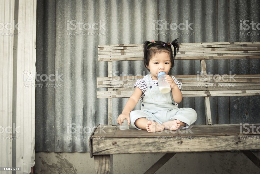 asian baby girl with bottle of milk sitting alone on table stock photo