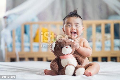Asian baby sit with teddy bear on ther bed in bedroom