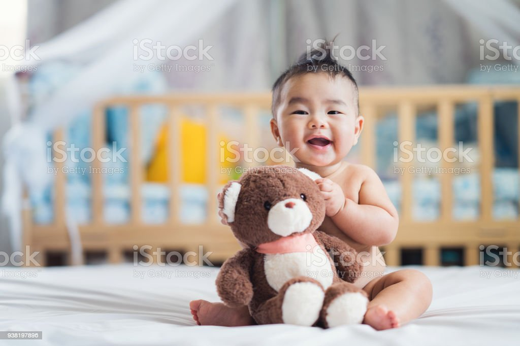 Asian baby sit with teddy bear stock photo